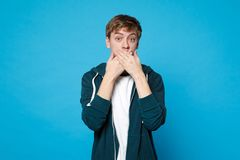 Portrait of shocked young man in casual clothes covering mouth with hands isolated on blue wall background in studio. People sincere emotions, lifestyle royalty free stock photo