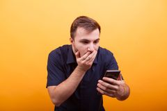 Portrait of shocked young man looking at mobile phone on yellow background. Holding cell phone stock image