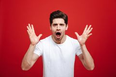 Portrait of a shocked young man in white t-shirt. Looking at camera with open mouth isolated over red background Royalty Free Stock Image