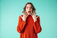 Portrait of a shocked young woman dressed in sweater. Looking at camera isolated over blue background Royalty Free Stock Photo