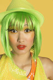 Portrait of shocked young woman with green hair against yellow background Stock Photos