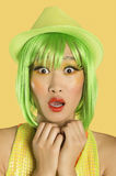 Portrait of shocked young woman with green hair against yellow background Royalty Free Stock Photos