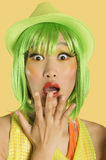 Portrait of shocked young woman with green hair against yellow background Royalty Free Stock Images