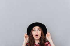 Portrait of a shocked young woman in hat looking up. At copyspace isolated over gray background Royalty Free Stock Image
