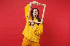 Portrait of shocked young woman in yellow fur sweater keeping mouth wide open, hold picture frame isolated on red. Background in studio. People sincere emotions royalty free stock image
