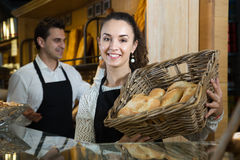 Portrait of shop assistant woman with basket of loaves Royalty Free Stock Photography