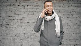 Portrait shot of afro-american man talking on phone. Handsome african-american guy in a coat and scarf speaking on stock video