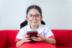 Portrait shot of Asian little girl in student uniform using smar Royalty Free Stock Photos