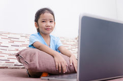 Portrait shot of asian little girl using laptop computer at home Royalty Free Stock Photo