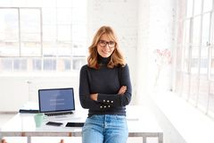 Confident businesswoman smiling to you and looking at camera while standing in the office stock photo