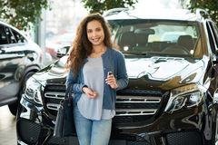 Capturing Moment of Buying New Car. Portrait shot of attractive mixed race woman looking at camera with charming smile after buying car of her dream, interior of Royalty Free Stock Images