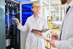 Adjusting Equipment with Colleague. Portrait shot of attractive technician wearing white coat and eyeglasses trying to adjust equipment at production department royalty free stock photo