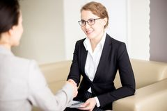 Shaking Hands with Business Partner. Portrait shot of attractive young manager wearing eyeglasses shaking hand of business partner after completion of productive stock photos