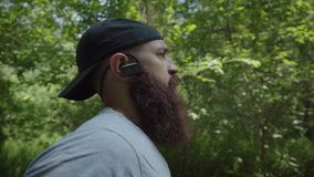 Portrait shot. A brutal man with a beard runs in the forest. Sporty caucasian man in headphones jogging in the green park. Outdoors. Portrait shot. A brutal man stock footage