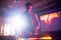 Handsome DJ Focused on Work. Portrait shot of handsome young DJ mixing music on console while entertaining guests at night club, lens flare stock photo