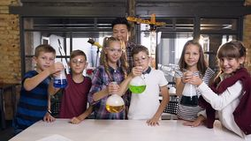 Portrait shot of Korean male teacher with group of six cheerful young caucasian students wearing goggles during chemical stock video footage