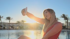 Portrait shot of pretty blond woman red swimsuit is making selfie with smart phone while relaxing near the swimming pool stock footage