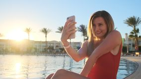 Portrait shot of pretty blond woman red swimsuit is making selfie with smart phone while relaxing near the swimming pool stock video footage