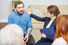 Sad Participant of Group Therapy Session. Portrait shot of sad bearded men sitting in circle and telling his life story to other patients while participating in Royalty Free Stock Images