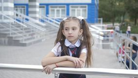 Portrait shot of the sad little girl in the school uniform in the school yard against the building of a primary school. stock footage