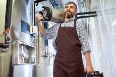 Bearded Brewer with Beer Kegs stock photography
