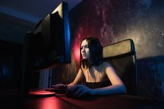 Portrait Shot of a Smiling Beautiful Professional Gamer Girl Playing in First-Person Shooter Online Video Game on Her. Personal Computer. Casual Cute Geek royalty free stock photography