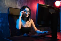 Portrait Shot of a Smiling Beautiful Professional Gamer Girl Playing in First-Person Shooter Online Video Game on Her. Personal Computer. Casual Cute Geek stock photo