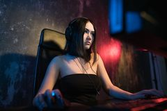 Portrait Shot of a Smiling Beautiful Professional Gamer Girl Playing in First-Person Shooter Online Video Game on Her. Personal Computer. Casual Cute Geek royalty free stock photo
