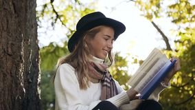 Portrait shot of smiling girl with beautiful scarf reading book in the city park. stock video