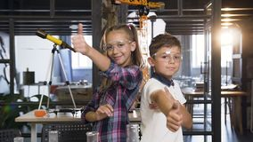 Portrait shot of two cheerful Caucasian scientist kids in safety goggles showing thumbs up in primary school chemical stock video