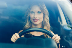 Portrait shot through windshield of blond pretty woman in car stock photography
