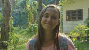 Young woman stand on countryside path in asian village and looking at camera. Portrait shot of young backpacker woman standing alone on a countryside path in stock video footage