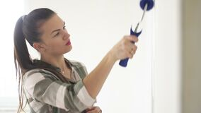 Portrait Shot of a Young Beautiful Woman Painting a Wall at Home. Work with a Roller. Apartment Renovations.