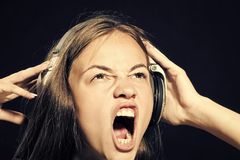 Portrait of shouting dj girl. Portrait of beautiful shouting dj girl holding hands earphones on head looking away with open mouth with no makeup on black Stock Images