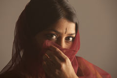 Portrait of a shy brunette indian woman with dark skin hiding her face Stock Images
