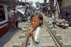 Portrait shy Filipino girl on railroad through slum Royalty Free Stock Photo