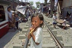 Portrait shy Filipino girl on railroad through slum Royalty Free Stock Photo