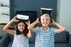 Portrait of siblings holding virtual reality headset in living room Royalty Free Stock Photos
