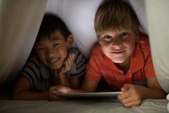 Portrait of siblings under bed sheet using digital tablet on bed Stock Image