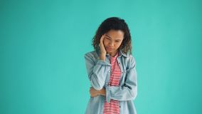 Portrait of sick African American woman suffering from headache touching head. Feeling bad standing on blue background. Unhealthy people and migraine concept stock video footage