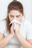 Portrait of sick brunette girl sneezing in paper tissue Royalty Free Stock Photo
