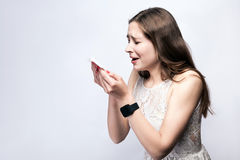 Portrait of sick cold woman with freckles and white dress and smart watch on silver gray background. Royalty Free Stock Image