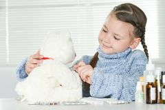 Portrait of a sick girl with white teddy bear. At home royalty free stock photography