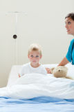 Portrait of a sick little boy on a hospital bed Stock Image