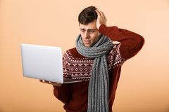 Portrait a sick man dressed in sweater and scarf isolated o. Ver beige background, browsing, holding laptop computer stock photos