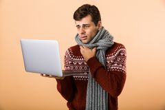 Portrait a sick man dressed in sweater. And scarf isolated over beige background, browsing, holding laptop computer stock photo