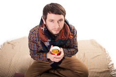 Portrait of a sick man with the flu coughing and holding a warm tea cup Stock Images