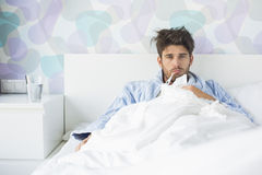 Portrait of sick man with thermometer in mouth reclining on bed at home Royalty Free Stock Photography