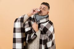 Portrait of a sick man wrapped in a blanket royalty free stock photography