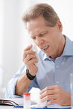 Portrait of sick man while wrinkling his nose. Allergic rhinitis. Serious male person keeping his eyes closed showing tooth while wiping his cheek Royalty Free Stock Images